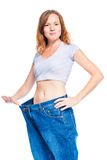 Slender red-haired girl showing old pants after losing weight. On white background Royalty Free Stock Image