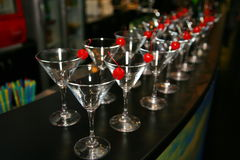 Slender rows of empty cocktail glasses on the bar. Decorative red cherry Stock Photography