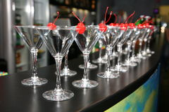 Slender rows of empty cocktail glasses on the bar. Decorative red cherry Royalty Free Stock Images