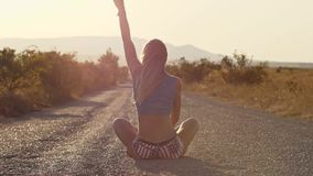 A slender sexy blonde is sitting on the road She triumphantly raises her hand to the Top