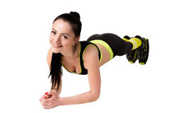 Slender smiling girl in kangoo jumps shoes doing plank exercise. Stock Images