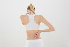 Slender sporty woman touching her injured nape Stock Photo