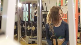 A slender strong girl trains a triceps in a crossover in the gym. A slender strong girl trains a triceps in a crossover in the gym, she unbends her hands down stock footage
