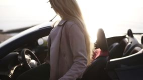 Slender, stylish girl with long blonde hair gracefully open the driver`s door of her black, sporty cabriolet car. Woman. Wearing beige leather jacket and modern stock footage