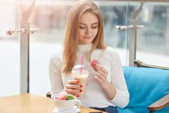 Slender sweet positive female holding plastic cup with coctail and one pink macaroon, going to have bite, looking at it. Attentively, sitting at table in stock image