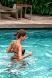 Slender tanned woman swimming at the pool. Rest and spa. Close up.  stock photo