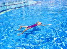 Slender teenage girl swims on her back in the outdoor pool stock image