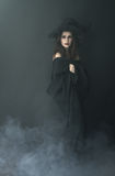 Slender witch in a smoke on  black background Stock Photo