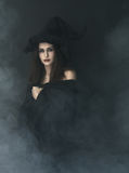 Slender witch in a smoke on  black background Stock Image