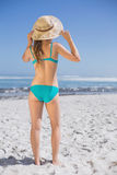 Slender woman in bikini on beach wearing sunhat Royalty Free Stock Image