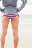 Slender woman in bikini bottom and gray jacket at beach Royalty Free Stock Photos