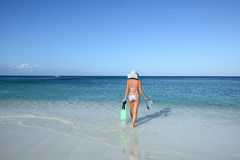 Slender woman in a bikini goes to swim in the sea Royalty Free Stock Images