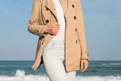 Slender woman in coat and jeans walking along the coast  Royalty Free Stock Photography