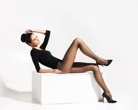 Slender woman with hot legs posing on a cube Stock Images