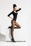 Slender woman with hot legs posing on a cube Royalty Free Stock Photography