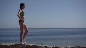 Slender woman jogger makes warm up of her legs on the beach