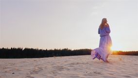 A slender woman in a light blue dress standing on the beach at sunset. The wind plays with her dress stock video footage
