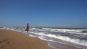 A slender woman in a long light dress is walking along the sandy beach on the incoming waves of a summer day. A slender woman in a long dress walks along a stock footage
