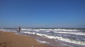 A slender woman in a long light dress is walking along the sandy beach on the incoming waves of a summer day. A slender woman in a long dress walks along a stock video footage