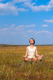 Slender woman meditate  in the meadow Stock Photography