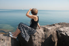 The slender woman on the shore Michigan Lake. The slender woman on the Lake Michigan shore watches for sailing vessel Stock Photography