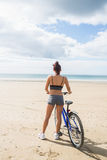 Slender woman standing with bike on the beach Royalty Free Stock Photography