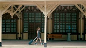 Woman is at the Train Station with Suitcase Departing to Holiday Summer Journey. Slender Woman with Suitcase is at the Cinematic Train Station in a Small Town stock footage