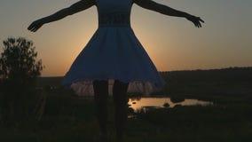 Slender Woman Turns Around in Her White Folk Dress at Nice Sunset stock video