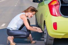 Slender woman unscrews spanner car wheel Royalty Free Stock Photos