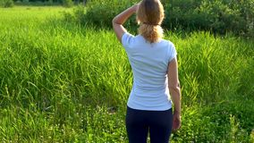 A slender woman walks barefoot on a green meadow with pink clover flowers on a Sunny summer day. stock footage