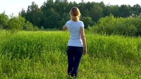 A slender woman walks barefoot on a green meadow with pink clover flowers on a sunny summer day. stock video