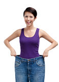 Slender woman wearing huge jeans Royalty Free Stock Photography