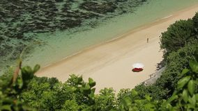 Slender woman in a white dress, a beach sunshade, a sunbed at some tropical seashore stock video