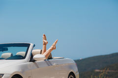 Slender women's legs look out of car window. Royalty Free Stock Photo