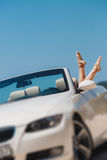Slender women's legs look out of car window. Royalty Free Stock Image
