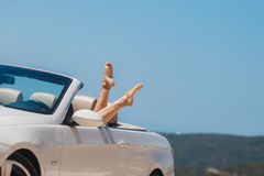 Slender women's legs look out of car window. Shapely barefoot female legs peeking out of a beautiful white convertible,standing on a background of mountains and Royalty Free Stock Image