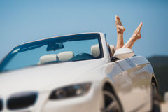 Slender women's legs look out of car window. Shapely barefoot female legs peeking out of a beautiful white convertible,standing on a background of mountains and Royalty Free Stock Photo