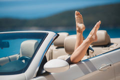 Slender women's legs look out of car window. Shapely barefoot female legs peeking out of a beautiful white convertible,standing on a background of mountains and Royalty Free Stock Images