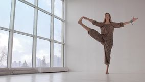 Slender yoga woman practicing extended hand-to-big-toe pose stock video footage