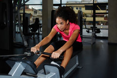 Slender young afro american woman doing exercises to strengthen the back. Attractive afro american woman with curly hair working out at gym doing legs exercise Stock Photo