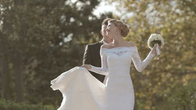 Slender young bride spinning in a park stock video footage
