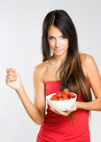 Slender young brunette holdng strawberries. Stock Photos