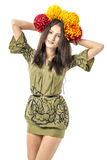 Slender young cheerful girl brown hair dances with a bouquet of colorful flowers on her head Stock Images