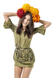 Slender young cheerful girl brown hair dances with a bouquet of colorful flowers on her head Royalty Free Stock Images