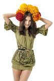 Slender young cheerful girl brown hair dances with a bouquet of colorful flowers on her head Royalty Free Stock Photos