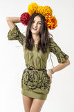 Slender young cheerful girl brown hair dances with a bouquet of colorful flowers on her head Royalty Free Stock Photography