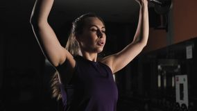 Slender young girl doing exercise with a barbell. The UPS and downs of weight. Evening training in the gym. Slender young girl doing exercise with a barbell stock footage