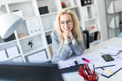 Young girl with glasses works in the office. A slender young girl in a white blouse, gray jacket and dark trousers is working in the office. The girl has white Stock Photo