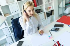 A young girl sits in headphones with a microphone at the desk in the office and makes notes in the document. A slender young girl in a white blouse is working Royalty Free Stock Photography