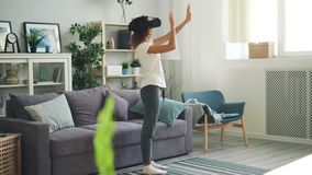 Slender young lady in casual clothing is using augmented reality glasses standing in light room at home and moving hands. Touching air. Devices, youth and stock footage